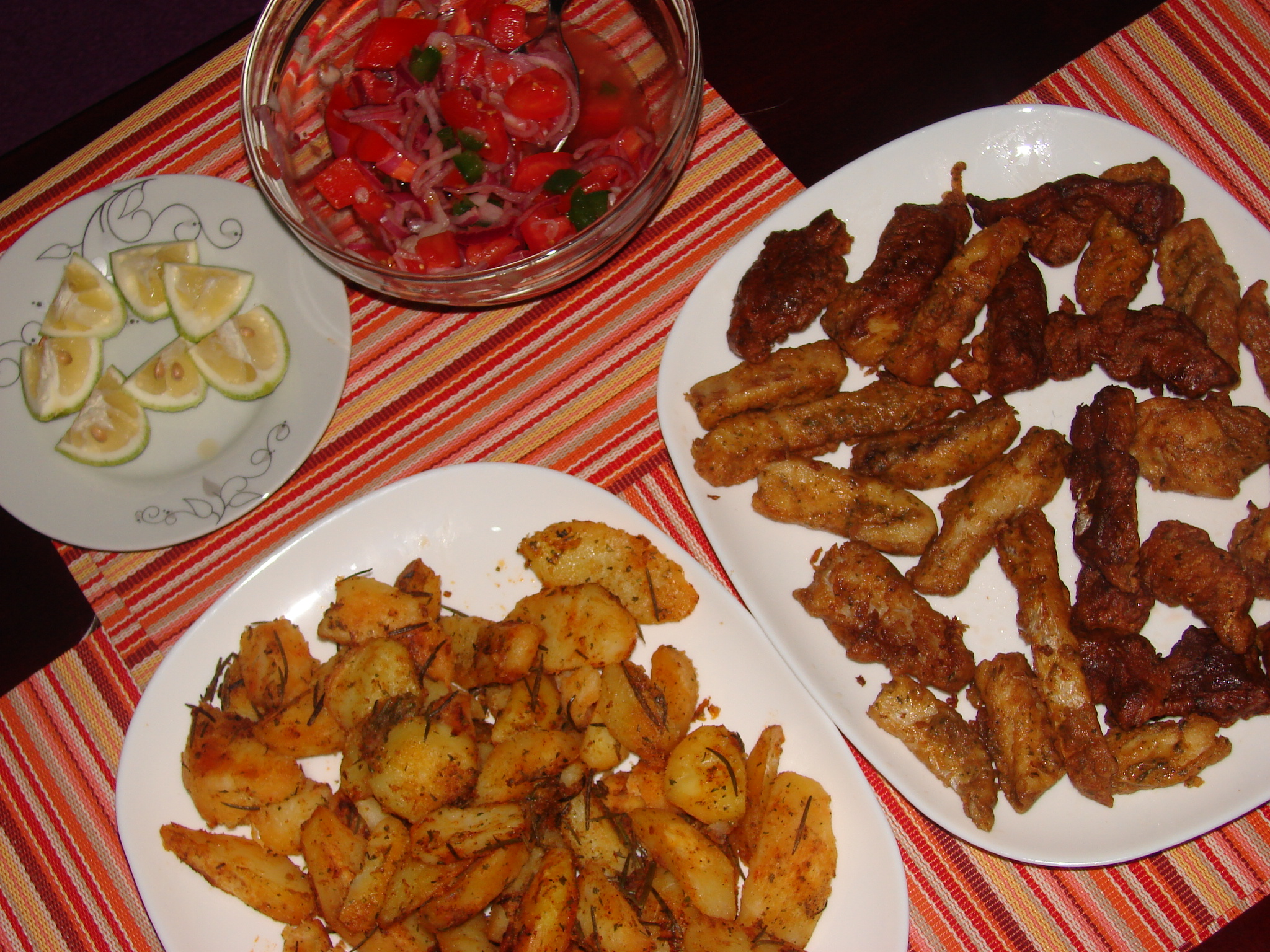 kachumbari, fish fingers, spicy potato wedges and lemon slices.